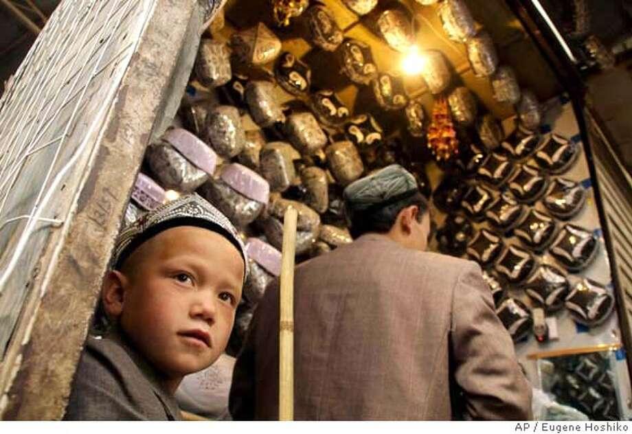 Young Uighur boy waits for customers to sell Muslim caps for men at Sunday Bazaar in Hotan, northwest China's Xinjiang Uighur Autonomous Region on Sunday, April 6, 2008. (AP Photo/Eugene Hoshiko) Photo: Eugene Hoshiko