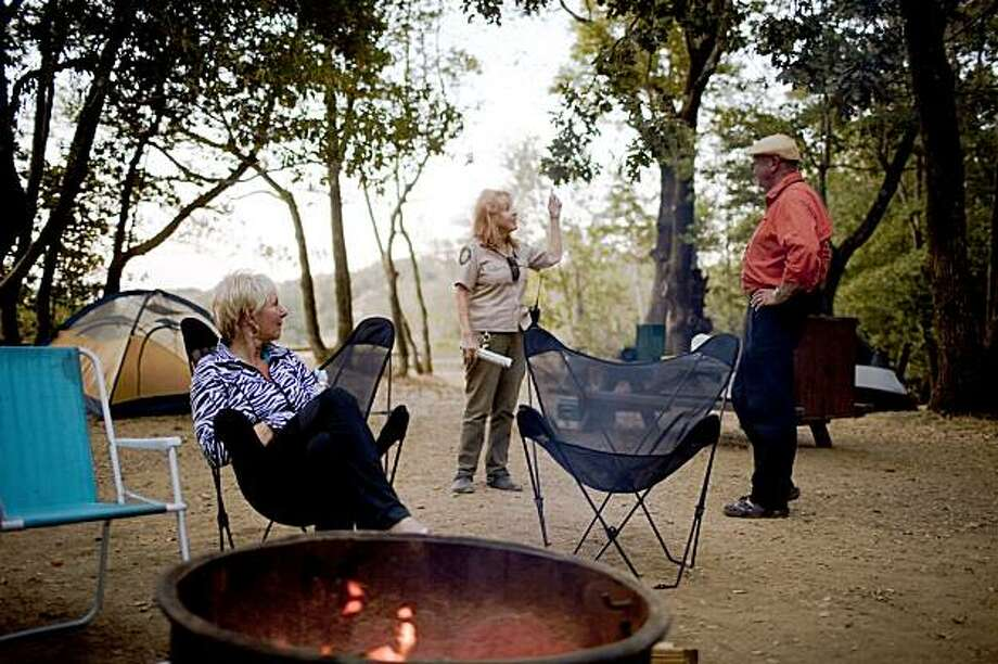 From left, Canadian tourist Gloria Bratland, and husband Allan Bratland, right, of Edmonton, Alberta, listens park aide Lorraine Taylor during an overnight stay at the at the China Camp State Park campground in Marin, Calif. on Friday, Aug. 28, 2009. The number of Californians traveling over the upcoming labor day weekend, according to the American Automobile Association, is expected it to be significantly lower than previous years as many schools are already back in session and the current economy. Photo: Stephen Lam, The Chronicle
