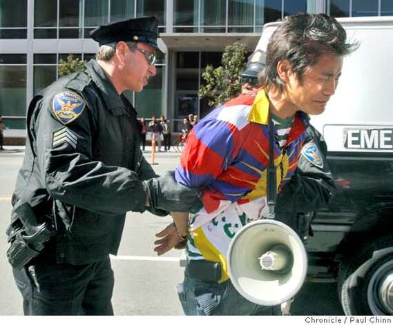 Police officers take a pro-Tibet protester into custody in front of AT&T Park before the Olympic torch relay in San Francisco, Calif., on Wednesday, April 9, 2008.  Photo by Paul Chinn / San Francisco Chronicle Photo: Paul Chinn