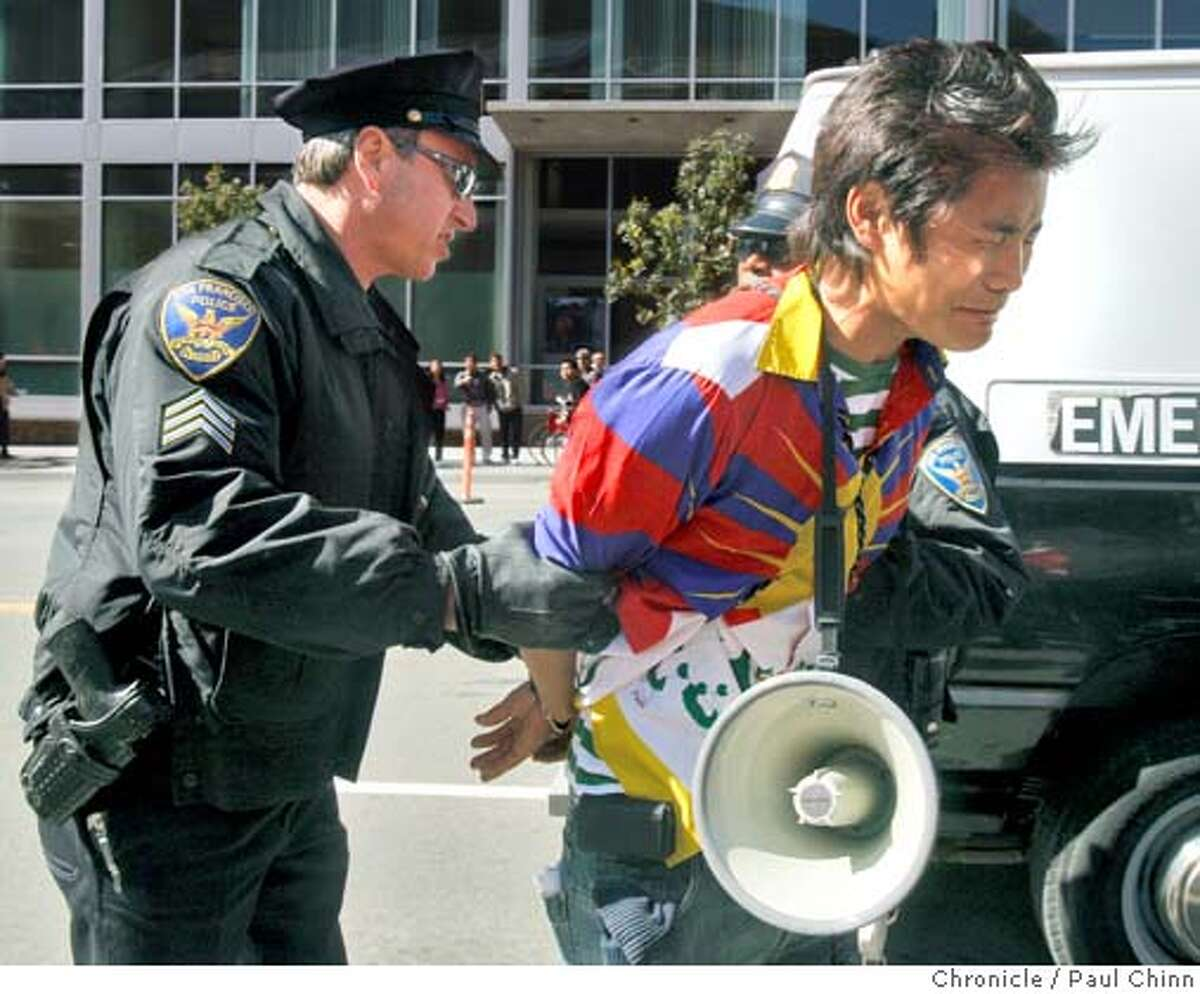 Police officers take a pro-Tibet protester into custody in front of AT&T Park before the Olympic torch relay in San Francisco, Calif., on Wednesday, April 9, 2008. Photo by Paul Chinn / San Francisco Chronicle