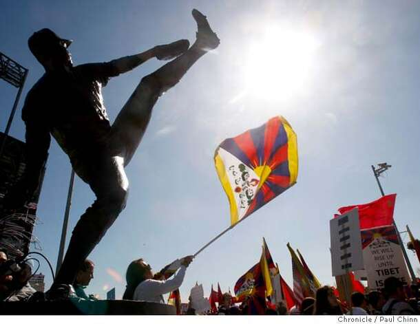 A demonstrator waves a Tibetan flag below the Juan Marichal statue at AT&T Park before the Olympic torch relay in San Francisco, Calif., on Wednesday, April 9, 2008.  Photo by Paul Chinn / San Francisco Chronicle Photo: Paul Chinn
