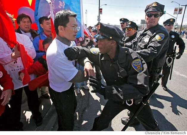 A San Francisco police officer pushes back a pro-Tibet Olympic Torch Relay demonstrator on Third Street south of the Lefty O' Doul Bridge in San Francisco, Calif. on Wednesday April 9, 2008. Photo by Kim Komenich / San Francisco Chronicle Photo: Kim Komenich