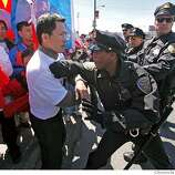 A San Francisco police officer pushes back a pro-Tibet Olympic Torch Relay demonstrator on Third Street south of the Lefty O' Doul Bridge in San Francisco, Calif. on Wednesday April 9, 2008. Photo by Kim Komenich / San Francisco Chronicle