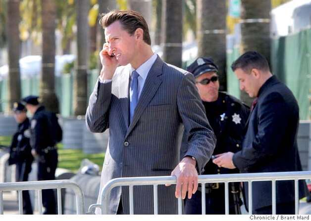 Mayor Gavin Newsom was using his cell phone as he viewed the scene on Market Street before the torch run. Thousands of protesters on both sides of the China issue protested near the Ferry building in San Francisco Wednesday, April 9, 2008. Photo by Brant Ward / San Francisco Chronicle Photo: Brant Ward