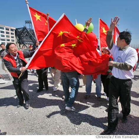A pro-Tibet protester is covered with Chinese flags as pro-China and anti-China protesters clash on Third Street south of the Lefty O' Doul Bridge in San Francisco, Calif. on Wednesday April 9, 2008 in anticipation of the passing of the Olympic torch. Photo by Kim Komenich / San Francisco Chronicle Photo: Kim Komenich