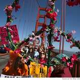 "CODEPINK members from left, Honne Heller and Adrienne Bolsega aka ""Opal Essence"" carry a flower covered peace sign as they join in a meditative peace walk lead by Burmese monk, Ashin Nanikabhivamsa across the Goloden Gate Bridge in San Francisco, Calif. on Wednesday, April 9, 2008.  Photo by Kat Wade / Special to the Chronicle"