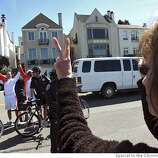 A woman signals peace to two Olympic bearers as they wait for the flame along Marina Blvd. in San Francisco, Calif., on Wednesday, April 9, 2008. Photo by Laura Morton / Special to The Chronicle