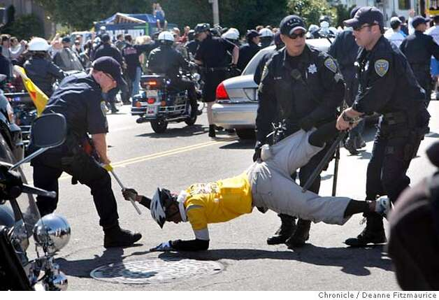 A flag carrying protester is brought down by the police as he tried to get into the street as the torch came by on Marina Blvd. The Olympic torch is carried through the streets on April 9, 2008 in San Francisco, Calif. Photo by Deanne Fitzmaurice / San Francisco Chronicle Photo: Deanne Fitzmaurice