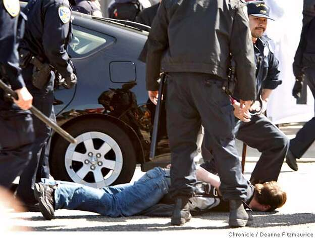 A protester is brought down by the police as he tried to get into the street as the torch came by on Marina Blvd.The Olympic torch is carried through the streets on April 9, 2008 in San Francisco, Calif. Photo by Deanne Fitzmaurice / San Francisco Chronicle Photo: Deanne Fitzmaurice