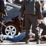 A protester is brought down by the police as he tried to get into the street as the torch came by on Marina Blvd.The Olympic torch is carried through the streets on April 9, 2008 in San Francisco, Calif. Photo by Deanne Fitzmaurice / San Francisco Chronicle
