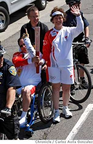 Two torch runners hold the torch and wave while carrying the torch on Wednesday afternoon during the Torch Relay on Wednesday, April 9, 2008, in San Francisco, Calif.  Photo by Carlos Avila Gonzalez / San Francisco Chronicle/ Pool Photo: Carlos Avila Gonzalez