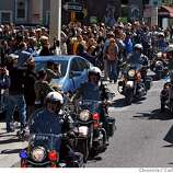 Spectators line Van Ness Avenue while police move up the street on motorcycles Wednesday afternoon during the Torch Relay on Wednesday, April 9, 2008, in San Francisco, Calif.  Photo by Carlos Avila Gonzalez / San Francisco Chronicle/ Pool