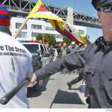An unidentified police officer shoves a protester away from the car that picked up six Olympic torch bearers from a bus that was blocked at the Embarcadero and Bryant Street, Wednesday April 9, 2008, in San Francisco, Calif. Photo by Lacy Atkins / San Francisco Chronicle