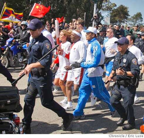 Appears to be former San Francisco Mayor Willie Brown carrying the torch on Marina Blvd as it feeds onto Doyle Drive under heavy police security the Olympic Torch photographed on Wednesday, April 9, 2008 in San Francisco.  Photo by Eric Luse / San Francisco Chronicle Photo: Eric Luse