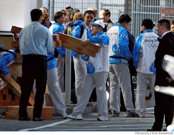 Men lift boxes holding replica Olympic torches outside buses that brought thethe Chinese Olympic Torch delegation to San Francisco International Airport on Wednesday, April 9, 2008, after a day of last-minute changes in the San Francisco Olympic Torch Relay  Photo by Kim Komenich / San Francisco Chronicle Photo: Kim Komenich