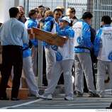 Men lift boxes holding replica Olympic torches outside buses that brought thethe Chinese Olympic Torch delegation to San Francisco International Airport on Wednesday, April 9, 2008, after a day of last-minute changes in the San Francisco Olympic Torch Relay  Photo by Kim Komenich / San Francisco Chronicle
