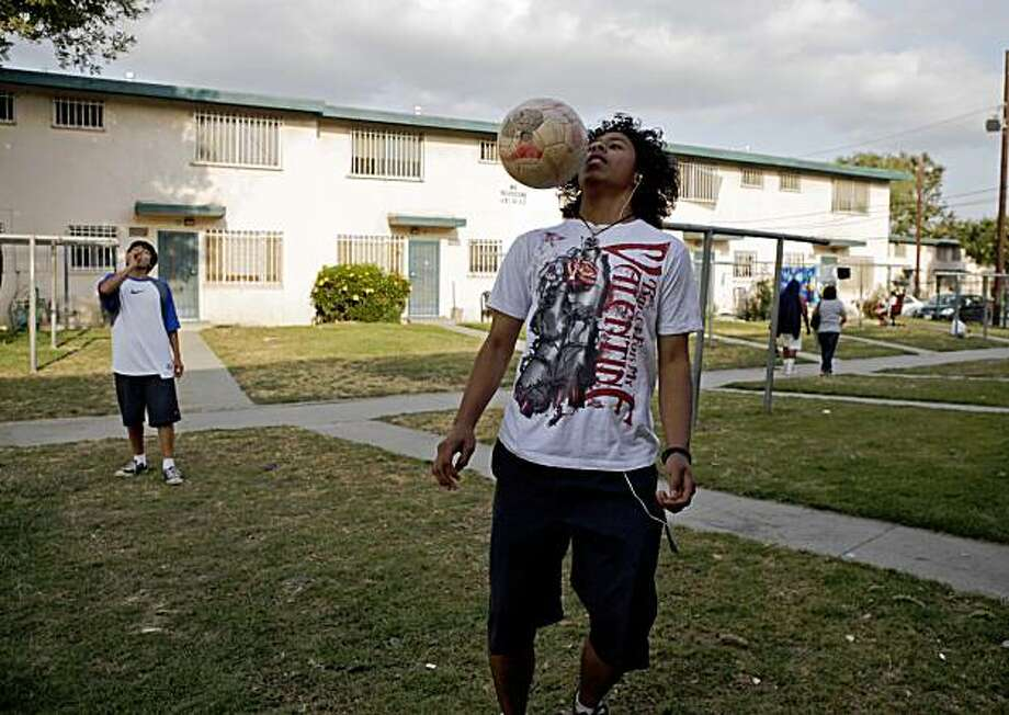 Daniel Rendon, 14, plays with a soccer ball at Jordan Downs housing project in the Watts section of Los Angeles, Wednesday, June 12, 2009. The Los Angeles Housing Authority plans to tear out a nearly 100 acre parcel of blight dominated by Jordan Downs, where just a third of the residents are employed and households earn 30 percent the city's average. In place of the notoriously drug- and gang-ridden housing project, the agency plans to build a mixed-income community with shops, offices and schools. (AP Photo/Jae C. Hong) Photo: Jae C. Hong, AP