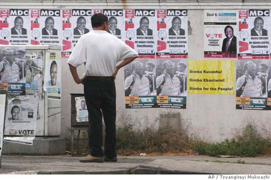 An unidentified man takes time to look at campaign posters on a street in Harare, Tuesday, April, 8, 2008. The main opposition party in Zimbabwe said that the Zimbabwean government was provoking its people by not releasing the results of the Presidential elections. The party appealed to neighbouring countries to intervene . (AP Photo/Tsvangirayi Mukwazhi) Photo: TSVANGIRAYI MUKWAZHI