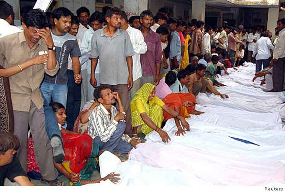 REFILE - CORRECTING PHOTOGRAPHER'S NAME Relatives of victims of a bus crash mourn in front of the bodies in a hospital compound at Bodeli village, about 170 km (106 miles) south of the western Indian city of Ahmedabad April 16, 2008. The bus veered off a bridge and plunged into a canal in western India on Wednesday, killing at least 44 school children and three adults, police said. REUTERS/Stringer (INDIA) Photo: STRINGER/INDIA