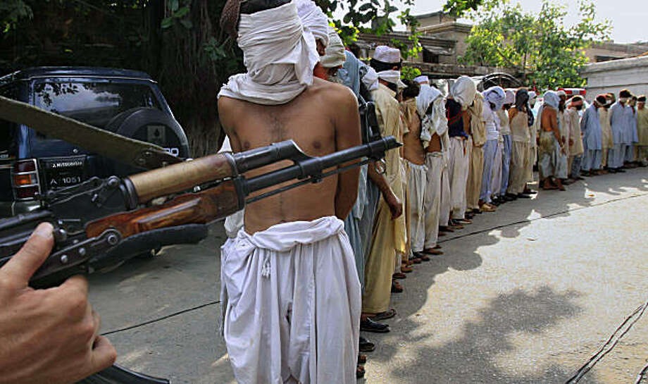 Pakistani soldier stands guard beside blindfold alleged militants, who were arrested during an offensive in the Khyber tribal region, Tuesday, Sept. 1, 2009 in Peshawar, Pakistan. Government forces destroyed four militant bases and killed 40 insurgents including two militants commanders, in Pakistan's northwestern border region. They also captured 43 suspected militants in the operation, authorities said. Photo: Mohammad Sajjad, AP