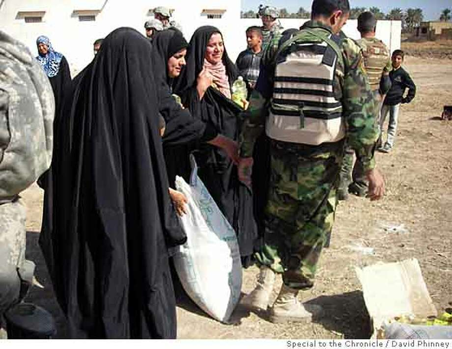 Iraqi women receive sacks of flour from U.S. troops in Baquba, Iraq. Ran on: 04-17-2008  U.S. troops hand out sacks of flour to Iraqi women in Baquba. Food distribution is another crucial part of the U.S. military's program. Photo: By David Phinney, Special To The