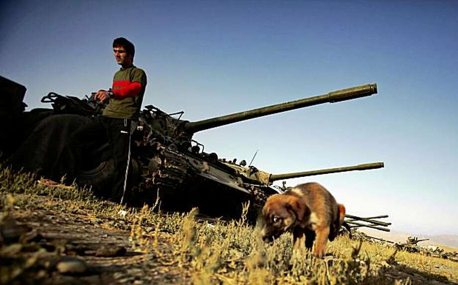 An Afghan soldier walks by the old Soviet-era tanks on the outskirts of Kabul, Friday, Aug. 28, 2009 in Afghanistan. (AP Photo/Dima Gavrysh) Photo: Dima Gavrysh, AP