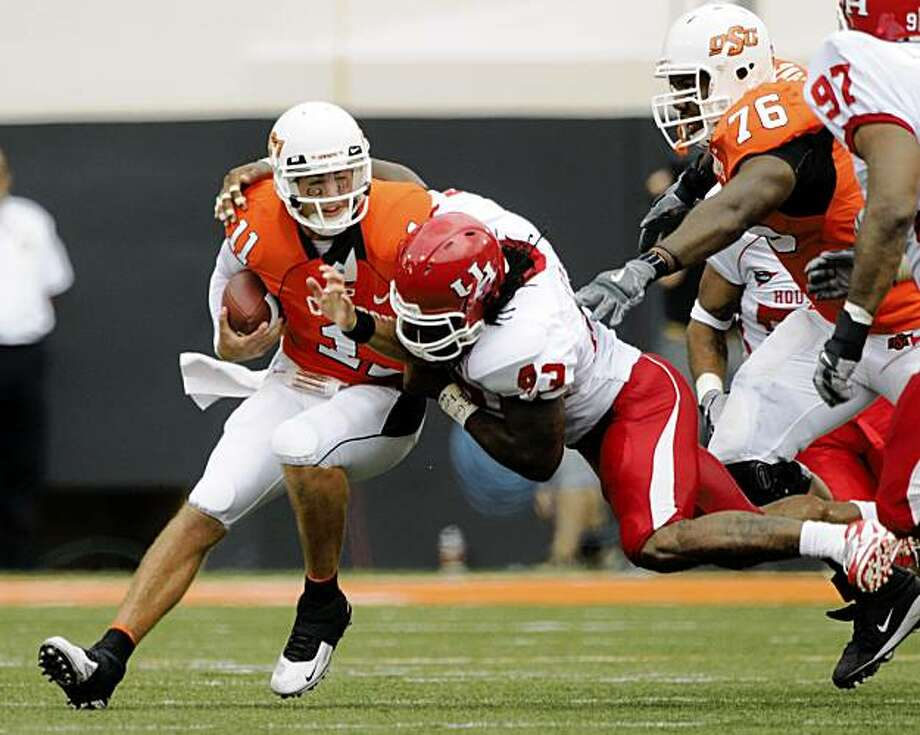 Oklahoma State offensive lineman, Russel Okung, right, watches as quarterback Zac Robinson, left, is sacked for a loss of 5 yards by Houston defensive end Tyrell Graham, center, during the first half of an NCAA college football game in Stillwater, Okla., Saturday, Sept. 12, 2009.(AP Photo/Brody Schmidt) Photo: Brody Schmidt, AP