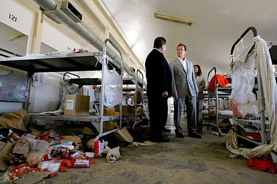 Gov. Arnold Schwarzenegger tours a prison room damaged in a riot, with Aref Fakhoury, left, acting warden for the California Institution for Men, left, and Norma Torres, Assembly member of the 61st District,  on Wednesday, August 19, 2009 in Chino, Calif.. Gov. Arnold Schwarzenegger on Wednesday toured the Southern California prison where 175 inmates were injured in a riot earlier this month, likening the devasation to a scene from one of his movies. (AP Photo/The Press-Enterprise, Stan Lim) ** NO SALES; MAGS OUT; MANDATORY CREDIT ** Photo: Stan Lim, AP
