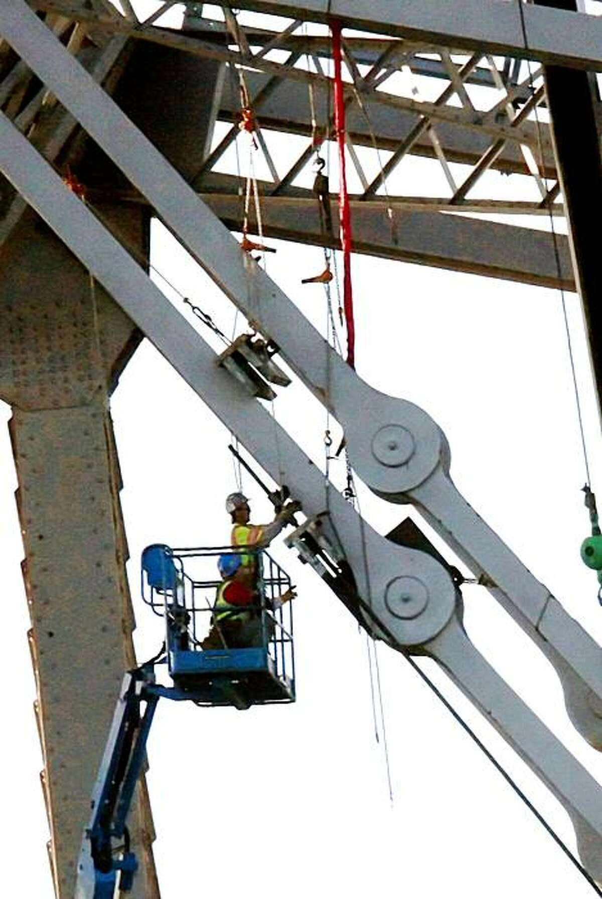 Workers work on the eastern tower of the Bay Bridge reinforcing a cracked eyebar on September 7, 2009 in Treasure Island, Calif.