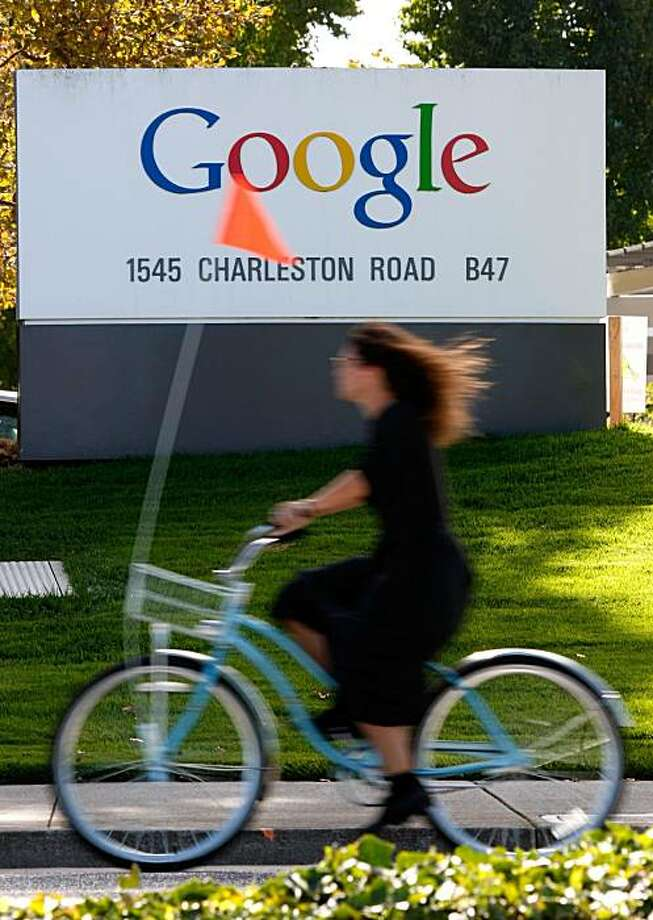 A Google employee rides a bicycle by a sign at the company's headquarters October 18, 2007 in Mountain View, California. It was reported on April 18, 2008 that shares of Google stock rose 20 percent to $539.41 on the Nasdaq. Photo: Justin Sullivan, Getty Images