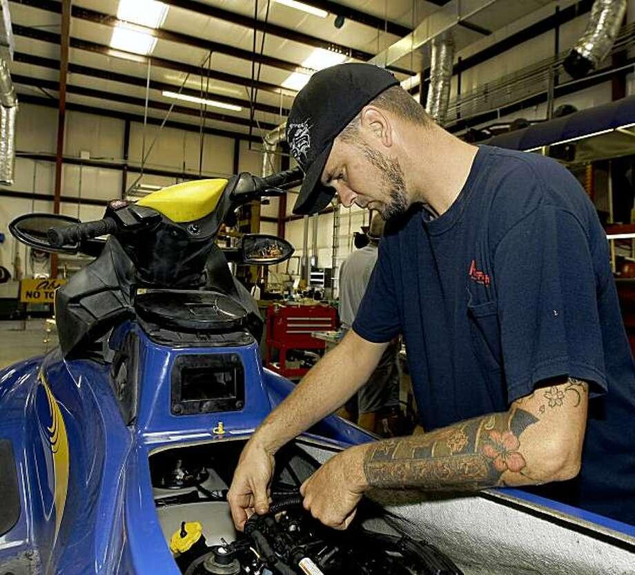 This photo taken Aug. 13, 2009 shows Jeremy Lavine working to repair a jetski  in Tampa, Fla. (AP Photo/Chris O'Meara) Photo: Chris O'Meara, AP
