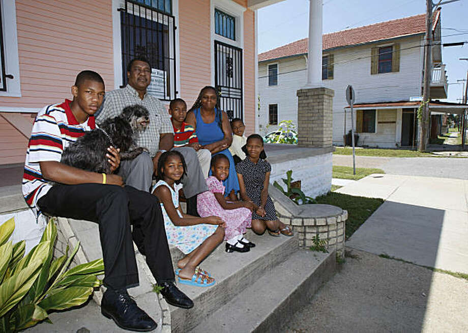 Collins and Shelia Phillips pose  wtih their grandchildren on the steps of their 9th ward home in New Orleans , Sunday, Aug. 23, 2009. Their home is still in the process of being renovated after Hurricane Katrina which struck the city in August of 2005. The children from top row from  left to right, 15-year old Jai Phillips, Collins Phillips, Jabari  Phillips, Shelia Phillips, Wendell Barnes, seated second row, Jyra Phillips, Joyia Phillips and Jayca Phillips.  (AP Photo/Bill Haber) Photo: Bill Haber, AP