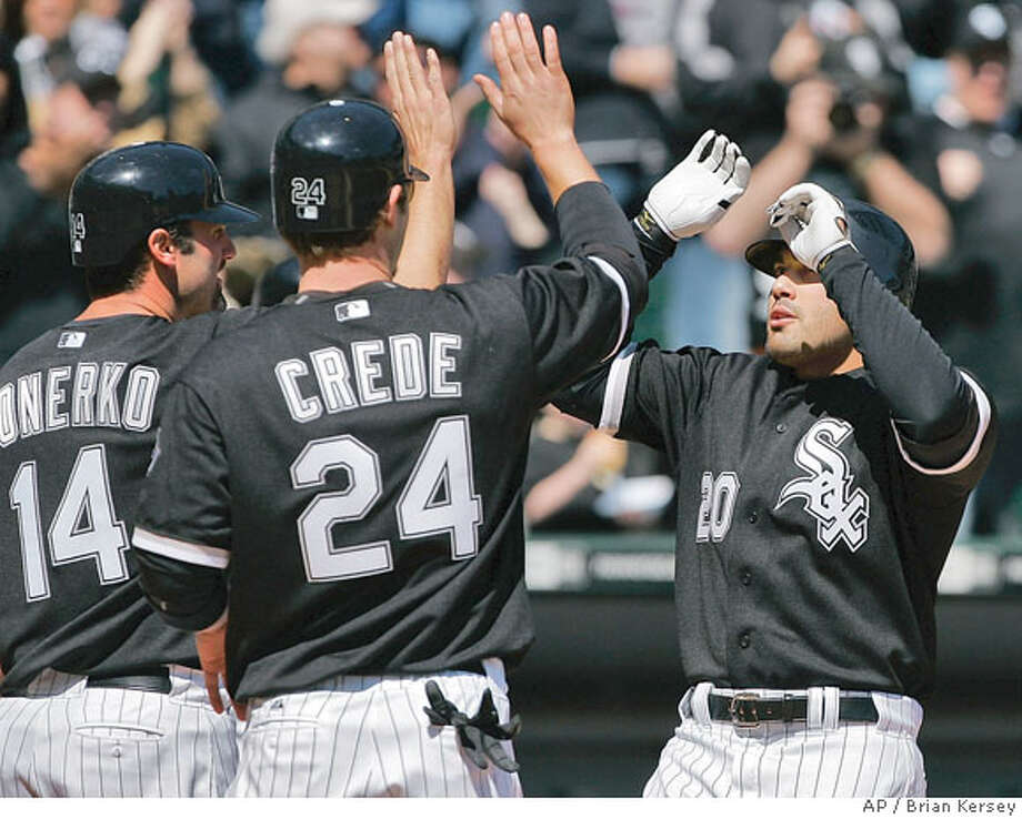 Chicago White Sox's Paul Konerko (14) and Joe Crede (24), high-five Carlos Quentin (20)at the plate after Quentin hit a three-run homer scoring them during the fourth inning of a baseball game against the Oakland Athletics in Chicago, Tuesday, April 15, 2008. (AP Photo/Brian Kersey) Photo: Brian Kersey