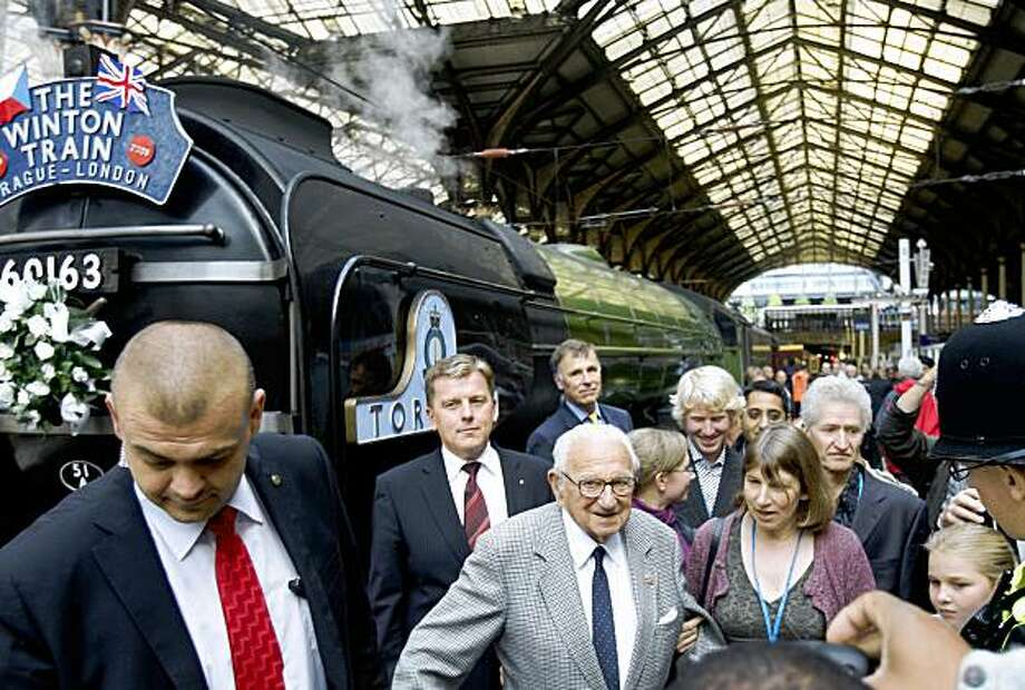 """Nicholas Winton, centre, who organized the Winton Train rescue of children 70 years ago is seen at Liverpool Street station in London, Friday, Sept. 4, 2009. The vintage train carrying Holocaust survivors pulled into London on Friday, ending a three-day trip across Europe that marked the 70th anniversary of their extraordinary rescue by a young British stockbroker.  Waiting to greet them at London's Liverpool Street Station was Nicholas Winton, age 100, who organized the rail """"kindertransports"""" that carried hundreds of mostly Jewish children from Nazi-occupied Czechoslovakia to safety in 1939.  (AP Photo/Kirsty Wigglesworth) Photo: Kirsty Wigglesworth, AP"""