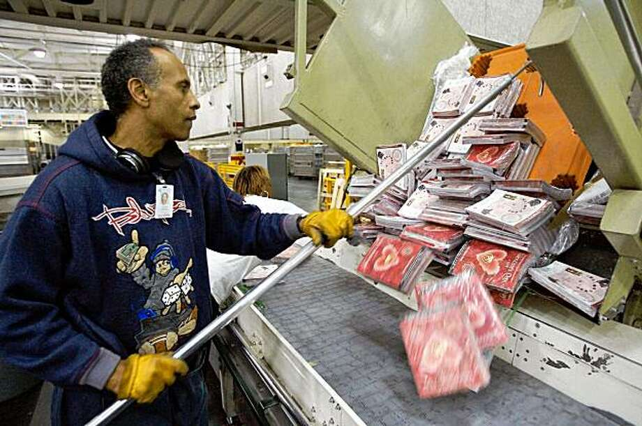 FILE - In this Jan. 28, 2008 file photo, a mail handler breaks bundles of business mail at the United States Postal Service Leslie N. Shaw Sr. Processing and Distribution Center in Los Angeles. Thanks to a one-two punch from the recession and rising production and shipping costs, retailers are shrinking catalogs, substituting postcards and slashing mailing lists. (AP Photo/Damian Dovarganes, File) Photo: Damian Dovarganes, AP