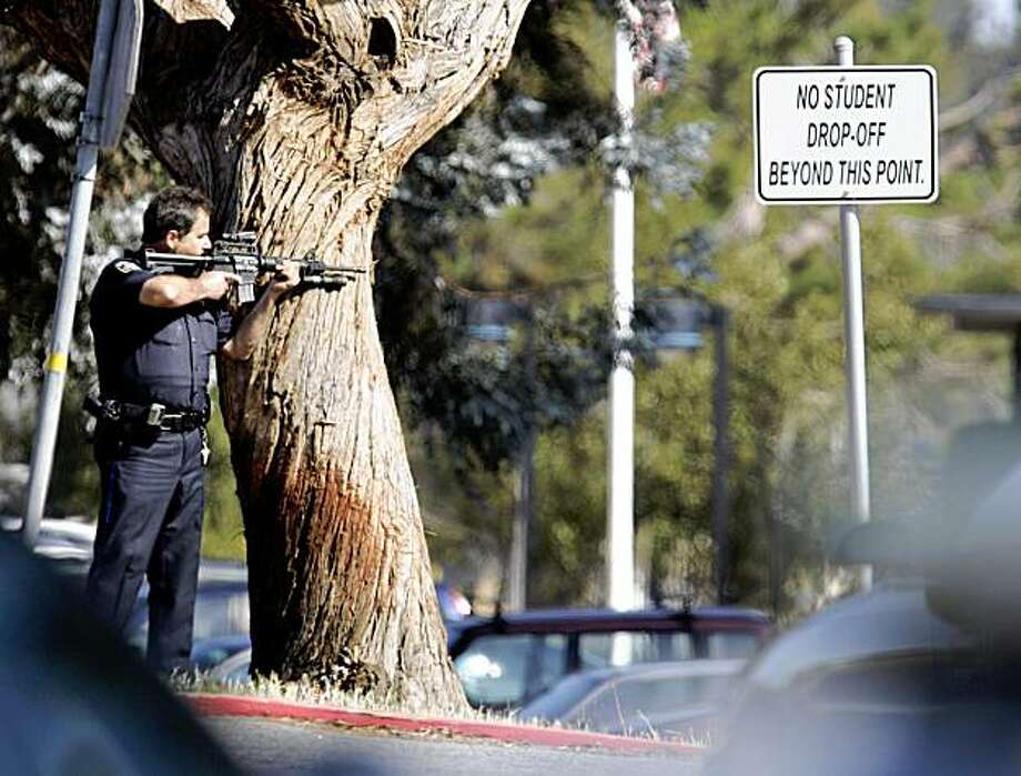 A police officer points his weapon towards Hillsdale High School in San Mateo, Calif., Monday, Aug. 24, 2009. Authorities say an explosion at this high school has forced evacuation of students and cancellation of classes. There are no reports of injuries. San Mateo police Lt. Mike Brunicardi says officers received several calls just after 8 a.m. Monday from teachers and staff reporting some kind of blast at the high school. (AP Photo/Paul Sakuma) Photo: Paul Sakuma, AP