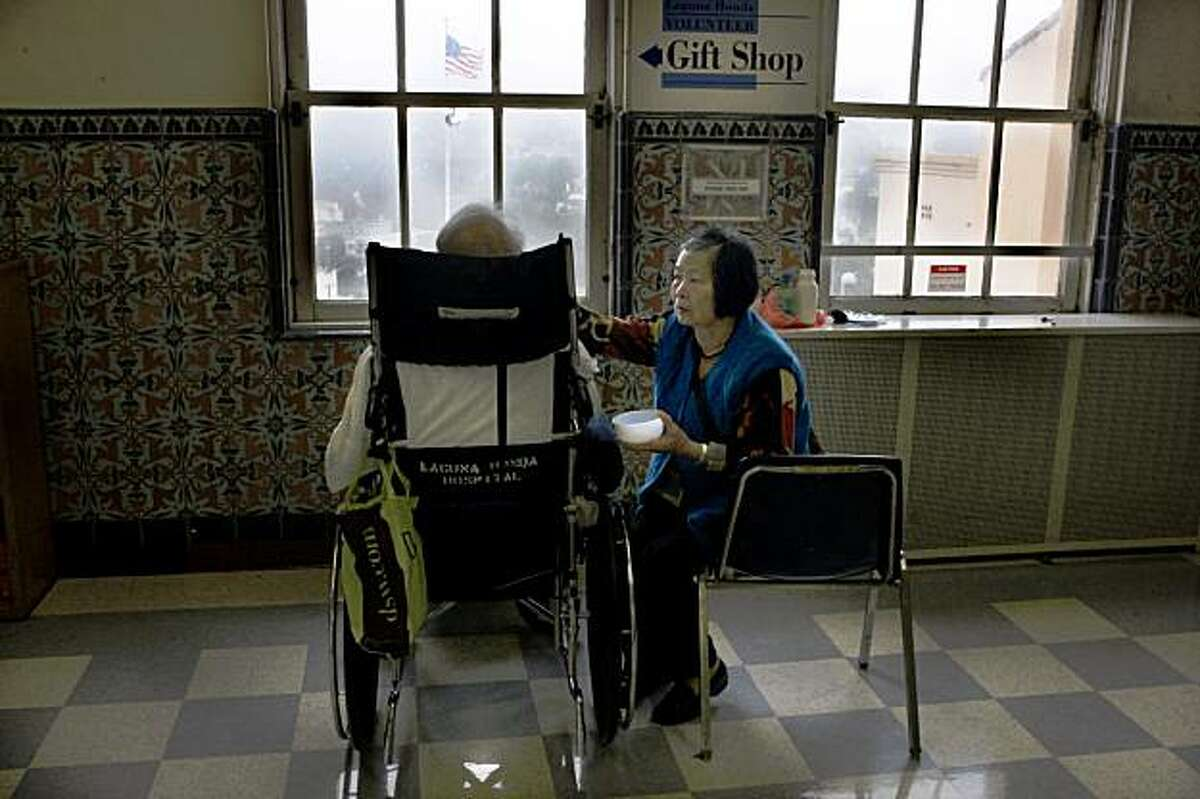 Cui Qim Liao Yu feeding her husband at Laguna Honda, the nation's largest city-funded nursing home in San Francisco, Calif., on Monday, July 20, 2009.