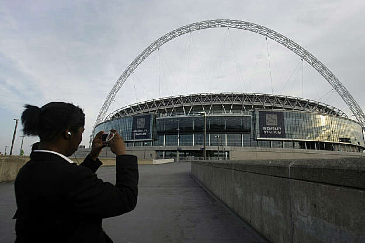 A youngster takes a photo of Wembley Stadium in London, Friday April 24, 2009. The Wembley Stadium turf will be dug up and replaced following criticism from football managers. The Football Association said Friday that the rye-grass playing surface will be replaced by a sand-soil turf in time for a semiprofessional cup final on May 9. (AP Photo/Matt Dunham)