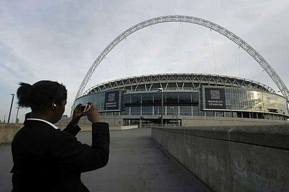 A youngster takes a photo of Wembley Stadium in London, Friday April 24, 2009. The Wembley Stadium turf will be dug up and replaced following criticism from football managers. The Football Association said Friday that the rye-grass playing surface will be replaced by a sand-soil turf in time for a semiprofessional cup final on May 9.  (AP Photo/Matt Dunham) Photo: Matt Dunham, AP