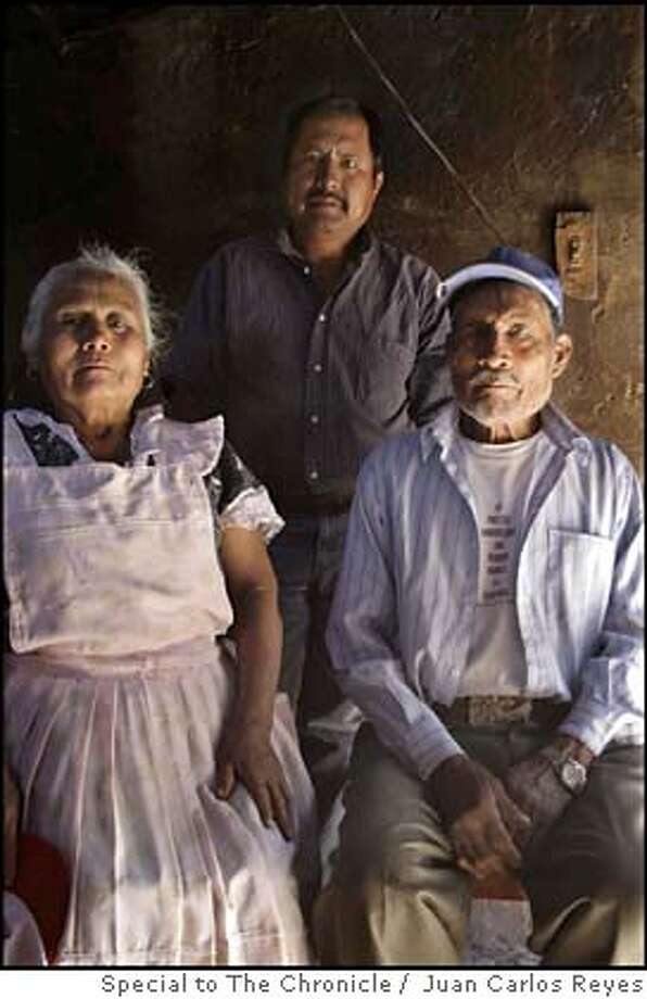 ###Live Caption:Jesus Leon, co-founder of a local environmental group, stands between his father, Agustin Leon, and mother, Guillermina Santos. Leon is at his parent's home in the town of San Isidro Tilantongo in the southern Mexican state of Oaxaca.###Caption History:Jesus Leon, co-founder of a local environmental group, stands between his father, Agustin Leon, and mother, Guillermina Santos. Leon is at his parent's home in the town of San Isidro Tilantongo in the southern Mexican state of Oaxaca.###Notes:###Special Instructions: Photo: By Juan Carlos Reyes, Special To