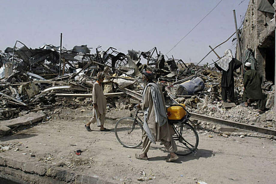 Afghans walk past the rubbles which were caused by Tuesday's explosion in the city of Kandahar province, south of Kabul, Afghanistan, Wednesday, Aug. 26, 2009. A cluster of vehicle bombs detonated simultaneously near a foreign-owned company that plans to build a road through an insurgent-held area. At least 41 people were killed, all civilians, officials said. (AP Photo/Allauddin Khan) Photo: Allauddin Khan, AP