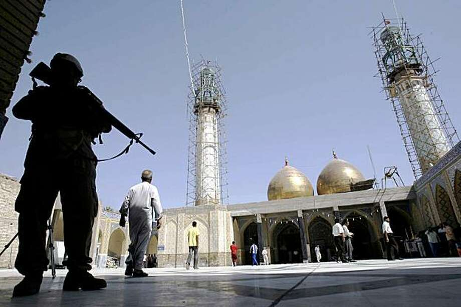 An Iraqi soldier stands guard at a Shiite shrine the morning after a parked car bomb attack nearby in Musayyib, 40 miles (60 kilometers) south of Baghdad, Iraq, Friday, Sept. 4, 2009. The blast on Thursday evening killed three and injured 35 people, police said. (AP Photo / Ahmed Alhusseiney) Photo: Ahmed Alhusseiney, AP