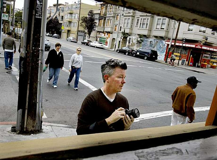 Brian Kusler (center) observes life at the corner of Church and 15th Streets with his Canon camera at the ready. Brian Kusler, who has a photograph published in the latest 7X7 magazine, loves photography and uses websites like Flickr to display his photographs. Photo: Brant Ward, The Chronicle