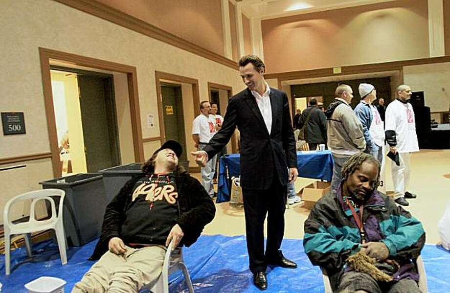Mayor Gavin Newsom chats with Esteban Diaz (left) who was getting a foot bath during Project Homeless Connect at the Bill Graham Civic Auditorium.  Newsom took a walk through of the event on Monday January 7, 2008. Photo: Laura Morton, Special To The Chronicle