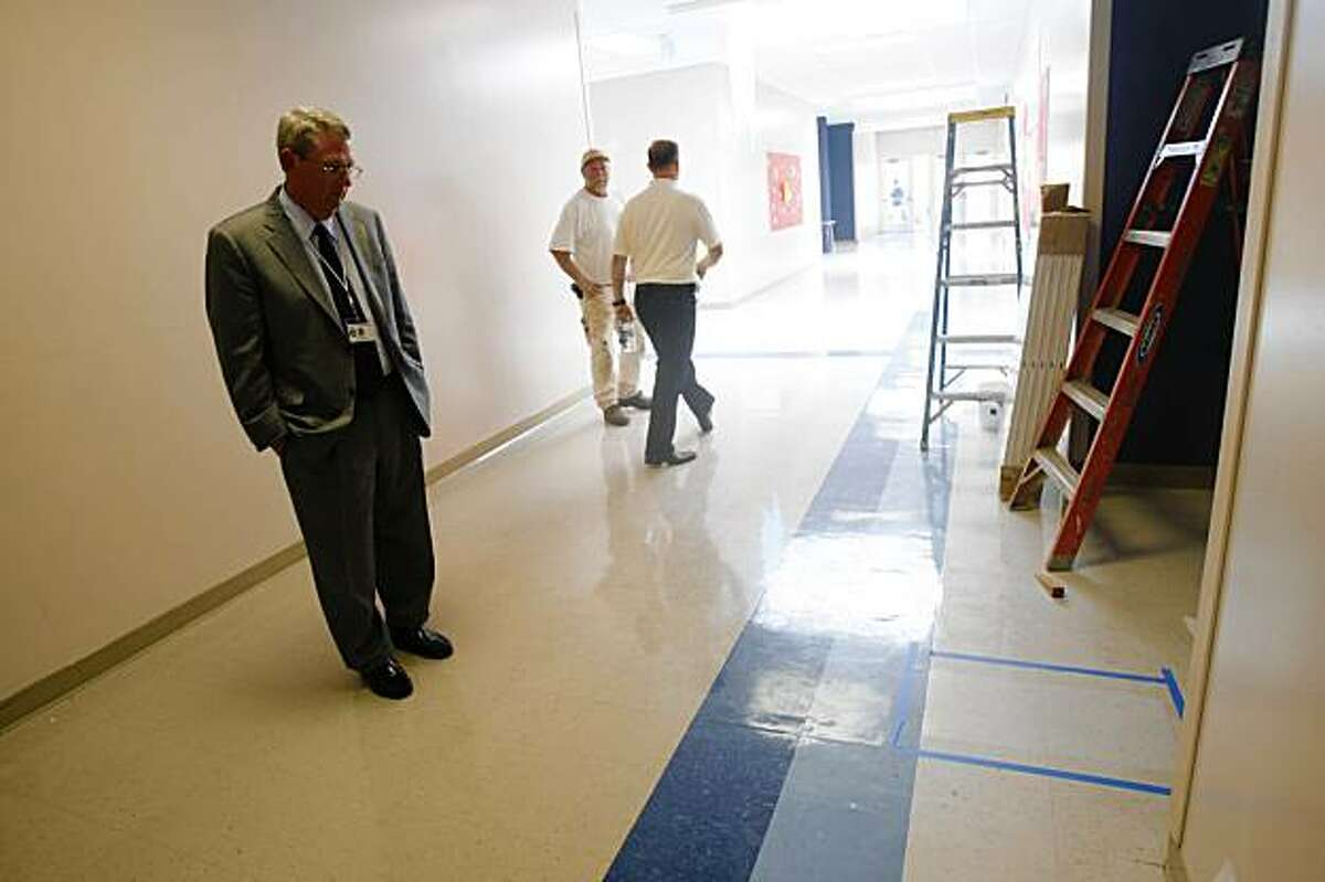 Scott Laurence (left), Superintendent San Mateo Union High School District, looks over the site where one of the explosions occurred at Hillsdale High School where repairs were being made in San Mateo, Calif. on Tuesday, August 25, 2009.