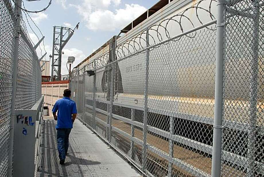 In this Monday July 20, 2009 photo, a pedestrian walks along the B and M Bridge that connects Matamoros, Mexico and Brownsville, Texas. When rail cars idle on side tracks in Mexico to be loaded with legitimate cargo and shipped to the United States, drug smugglers scan for places to hide their own loot _ and if no good place is apparent, they make one.  (AP Photo/Brad Doherty) Photo: Brad Doherty, AP