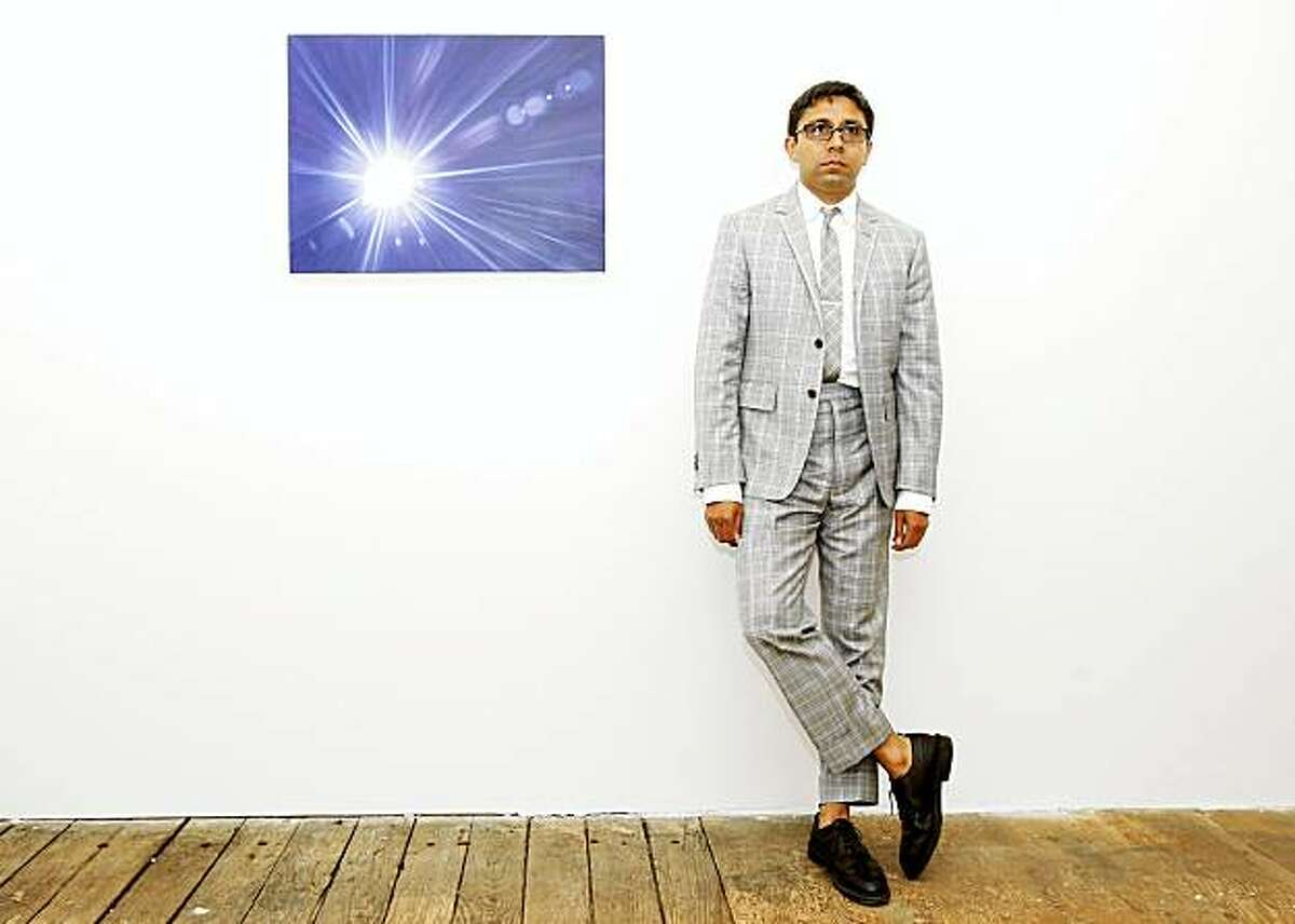 Chris Perez stands next to a painting by Jordan Kantor called Untitled (Basel lens flare 4496) in his gallery. Chris Perez runs the Ratio 3 gallery just off Valencia Street on Stevenson Street in San Francisco, CA.
