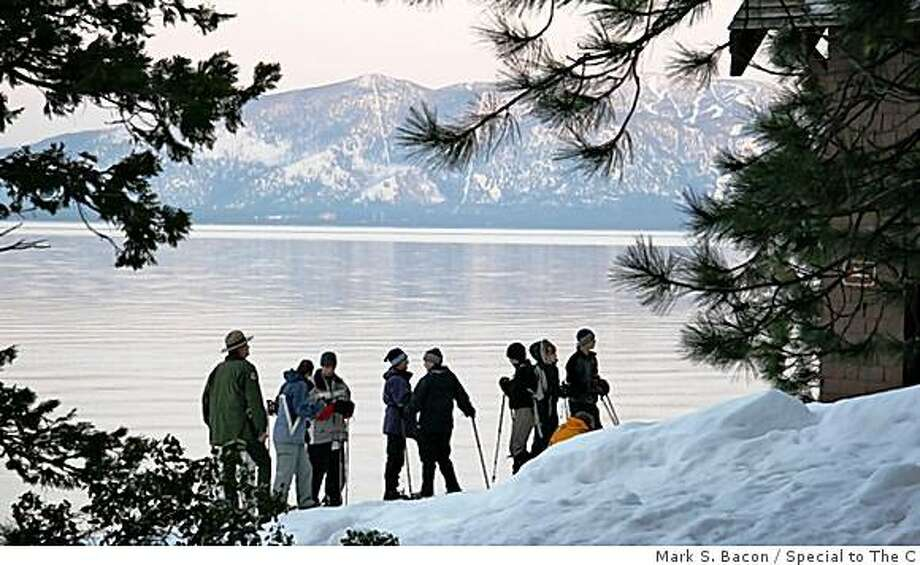 As sunlight fades, California Park Ranger Brian Barton and tour guests pause at the short of Lake Tahoe during a recent moonlight snowshoe tour of Ed Z'Berg - Sugar Pine Point State Park. Photo: Mark S. Bacon / Special To The C