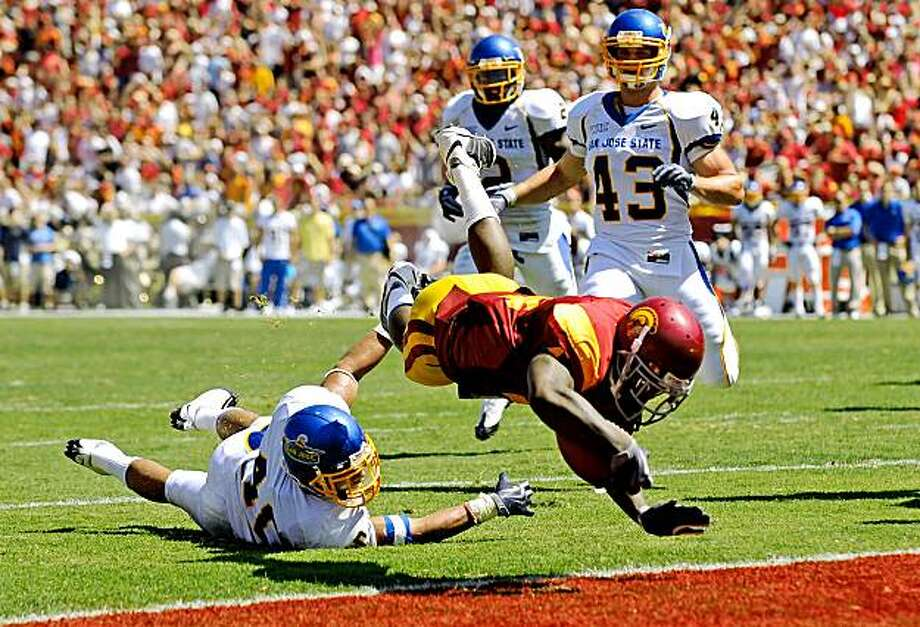 LOS ANGELES, CA - SEPTEMBER 05:  Joe McKnight #4 of the USC Trojans dives into the end zone to score a touchdown against Tiuke Tuipulotu #40 of the San Jose State Spartans during the second quarter at Los Angeles Memorial Coliseum on September 5, 2009 in Los Angeles, California.  (Photo by Kevork Djansezian/Getty Images) Photo: Kevork Djansezian, Getty Images