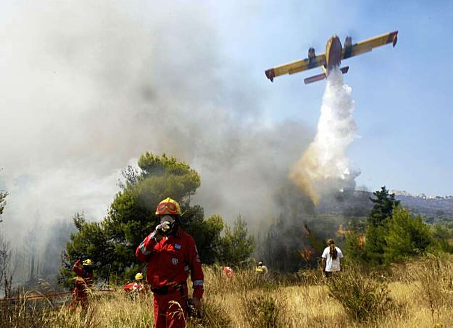 A plane drops water as firefighters try to extinguish a burning forest in Dioni, 40 kilometers (25 miles) east of Athens, Greece, Monday, Aug. 24, 2009. An overnight drop in gale-force winds offered hard-pressed Greek firefighters a brief respite Monday after wildfires raged unchecked for two days north of Athens, burning houses and swathes of forest while forcing thousands to flee their homes. Photo: Petros Giannakouris, AP